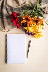 Masa üstünde not defteri, kalem ve çiçekler