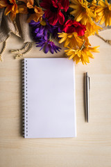 Notebook, diary, pen and flowers on the table