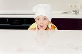 Playful child in a chefs hat or toque