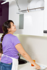 Woman placing clean dishes back on the rack