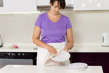 Housewife drying dinner plates after a meal