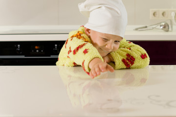 Young child stretching across a kitchen counter