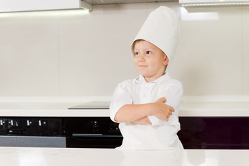 Confident smiling young boy in a chefs uniform