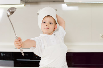 Young chef fencing with his stainless steel ladle