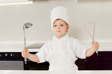Proud little boy chef holding up his utensils