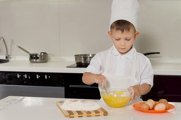 Little boy standing baking cakes in a toque