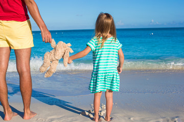 Close up bunny toy in hands of little girl and dad on sea