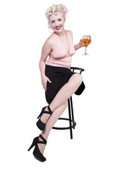 Woman in pin-up dress drinking on a chair - Isolated