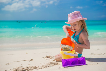 Adorable little girl playing with sand on a perfect tropical
