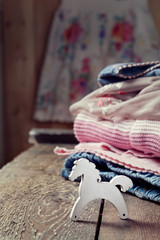 Various girls clothes and a small wooden toy horse