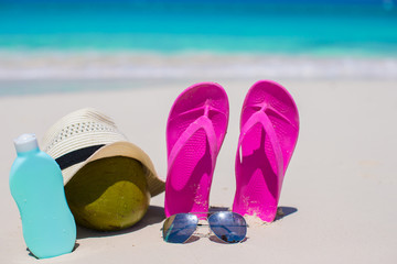 Flip flops, coconut, hat and suncream on white sand
