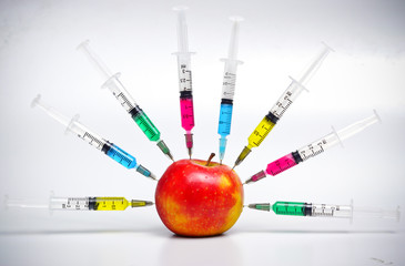 gmo apple surrounded by needles with chemical substances