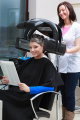 Woman reading magazine in hair beauty salon. By hairdresser.