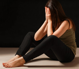 Depressed woman sitting on floor with eyes closed