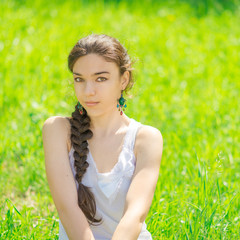 Portrait of a beautiful girl sitting on grass.