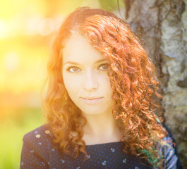 Portrait of red-haired young woman. With sunshine.