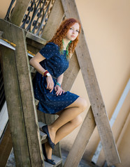 Beautiful redhead girl sitting on old wooden stairs.
