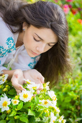Young woman smelling flowers in garden.