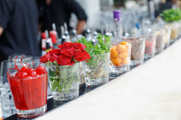 Cherries, herbs and flowers on bar counter
