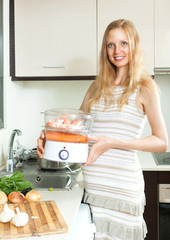 Happy  pregnant woman cooking vegetables and salmon in electric