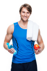 Sportsman in blue shirt holds water and apple.