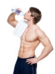 Handsome muscular sportsman drinks water.