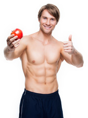 Young happy bodybuilder holding apple.