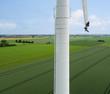 Leinwandbild Motiv Rotorenkletter an Windenergieanlage
