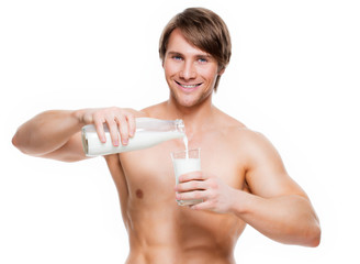 Young  muscular man pouring milk into a glass .