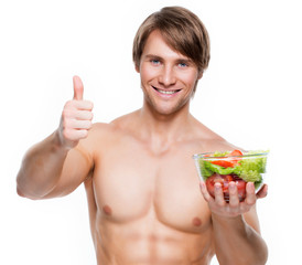 Happy muscular man holding a salad.