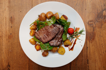 Steak with fried potatoes on wooden table