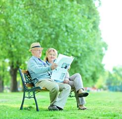 Mature man and woman reading the news outdoors