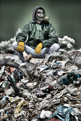 Man in a gas mask sitting on the garbage and holding a bone