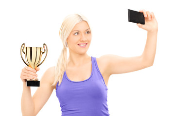 Blond woman holding a trophy and taking selfie