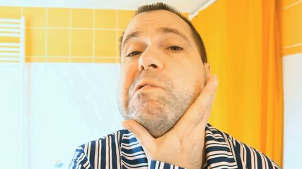 portrait of a man in pajamas shave his face in the bathroom