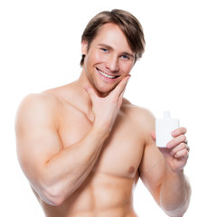 Young happy man applying lotion on face.