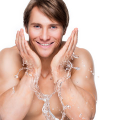 Smiling man washing his face with water.