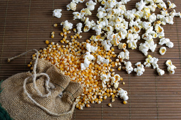 Popcorn spilled out of the jute bag over wooden background