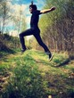 young man jumping over forest path