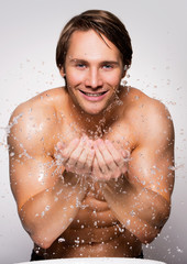 Smiling man washing his healthy face with water.