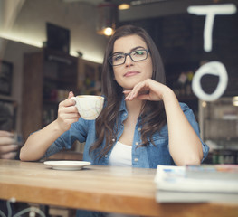 Portrait of beautiful woman drinking coffee at cafe