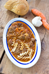 Beef goulash with pasta on wooden background