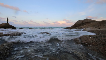 Evening scene of sea wave and stone reef