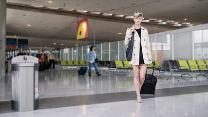 Businesswoman traveling with trolley at Charles de Gaulle airpor