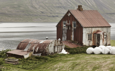 Iceland landscape in Seydisfjordur. Abandoned rusted farm and fi
