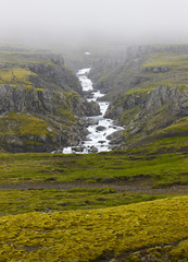 Iceland landscape in the east fiords. River and rocks with fog.