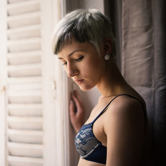 Sensual woman portrait in lingerie in front of a window.
