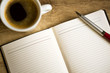 Notebook with coffee cup on wooden table