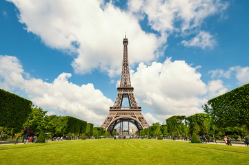 Eiffel Tower and gardens isolated against blue cloudy sky. Paris
