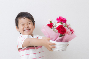 カーネーションの花束を持つ子供